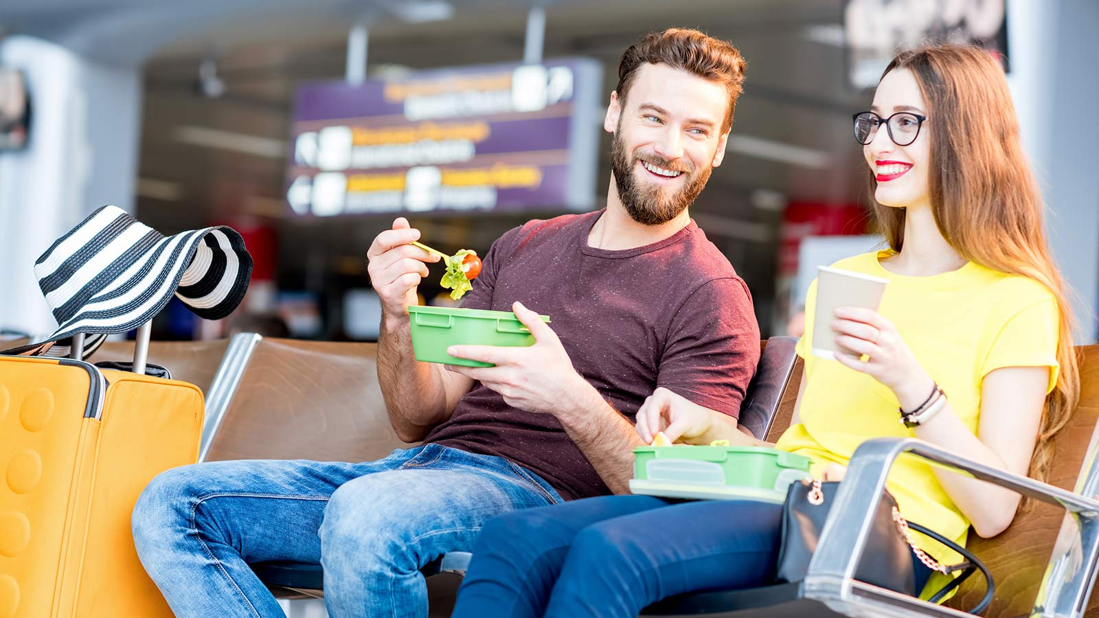 Couple eating salad in airport terminal