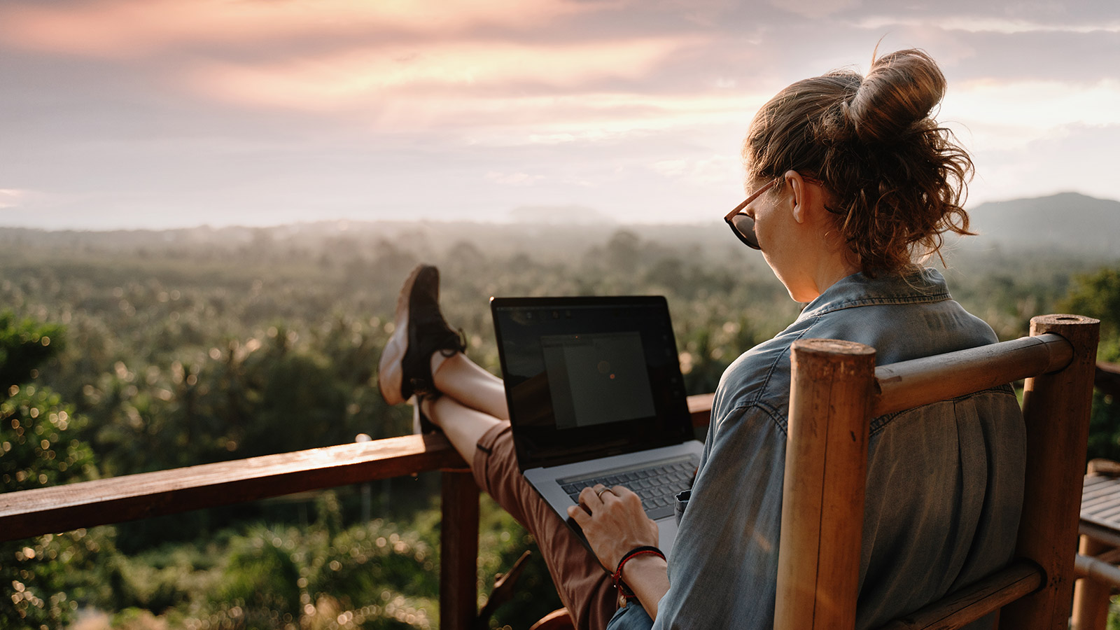 Young girl using a laptop at sunset
