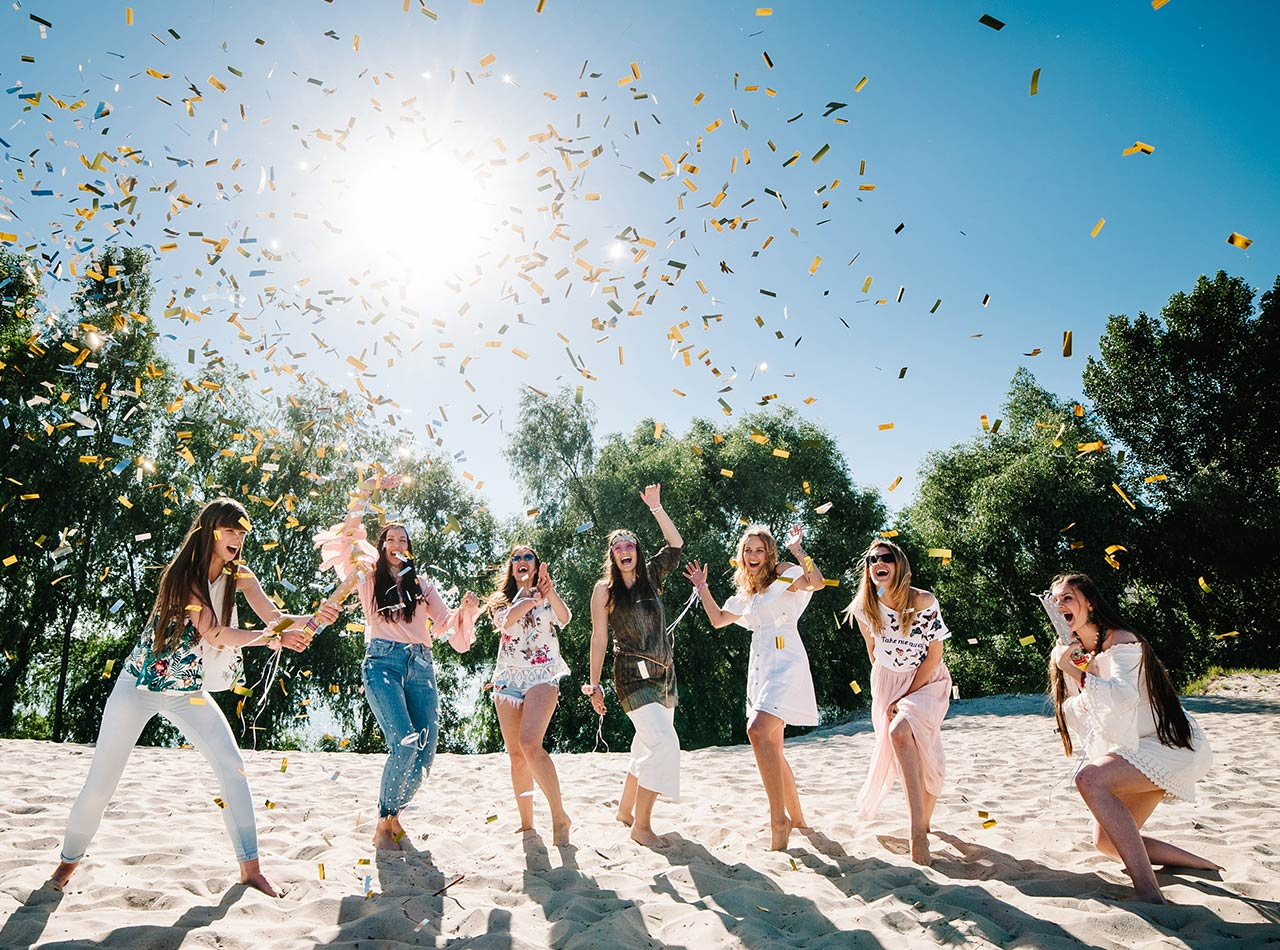 Group of young women throwing confetti on beach
