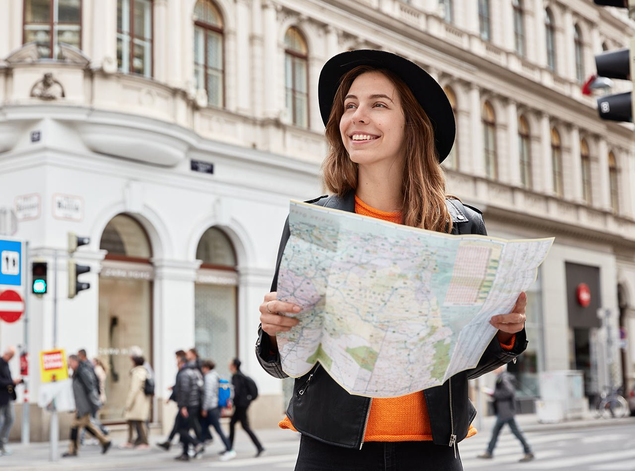 Young happy tourist holding paper map and looking out at city