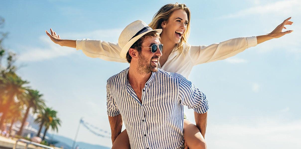 Joyful girl piggybacking on young man at beach resort